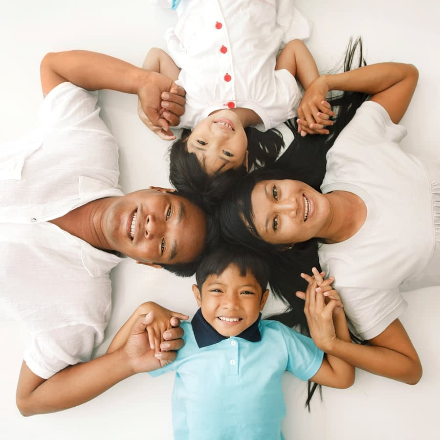 High angle view of cheerful Asian family lying down on the floor and holding hands. They are looking at camera.