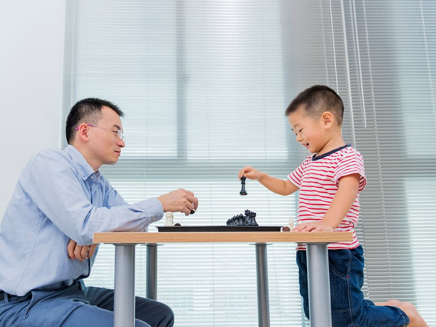 Father and son playing chess.